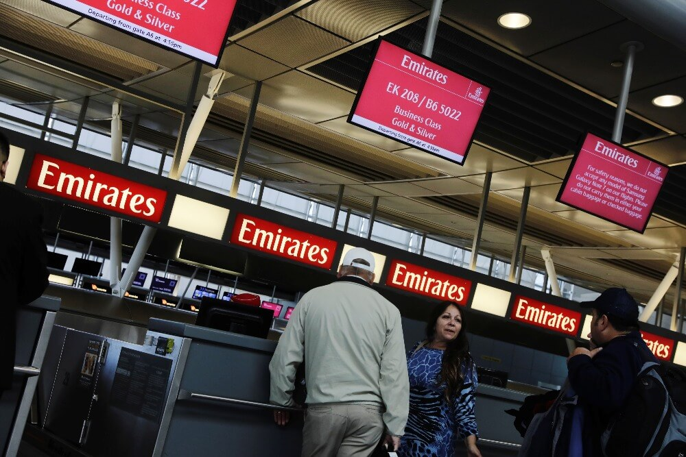 Travelers wait at an Emirates Airlines ticket desk at JFK International Airport in New York