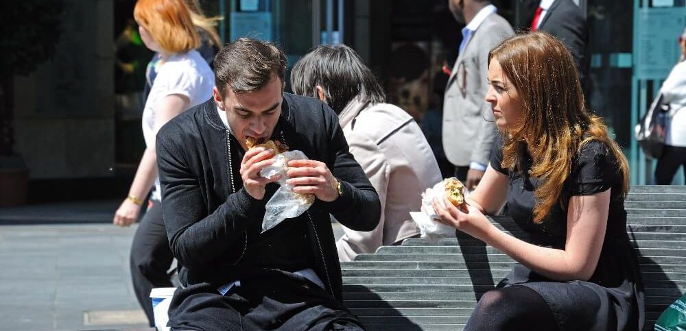 Couple sitting on a bench having a takeaway lunch