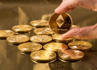 Hand holding a single ether or ethereum coin over bitcoins on gold background to illustrate blockchain and cyber currency
