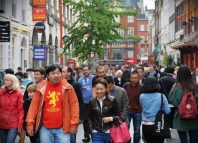 People walk along a busy shopping street in London's Chinatown