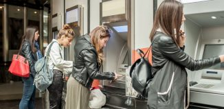 Four girl friends withdrawing money from credit card at ATM