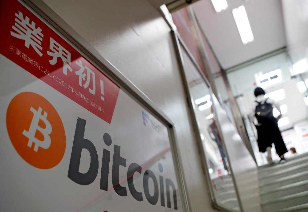 Logo of Bitcoin is seen on an advertisement of an electronic shop in Tok...