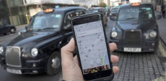 Uber app on a mobile telephone, as it is held up for a posed photograph, with London Taxis in the background, in London