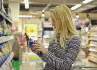 Woman in a supermarket standing in front of the freezer and choose buying pasta product