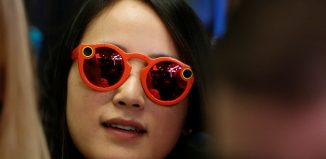 A woman wears Snapchat Spectacles on the floor of the New York Stock Exchange (NYSE) while waiting for Snap Inc. to list their IPO in New York