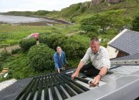 Brian Gardner and Ben Cormack fit solar thermal water heaters onto the roof of a cottage on the island of Eigg Inner Hebrides Scotland