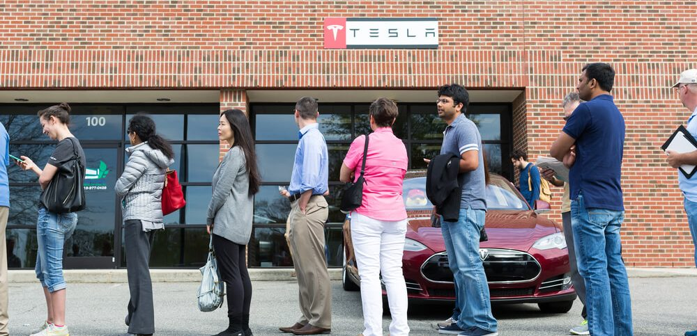 People queue at a Tesla Motors location to put down a reservation on a new Tesla Model 3