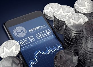 Smartphone with Monero trading chart on-screen among piles of silver Monero coins. Monero trading concept