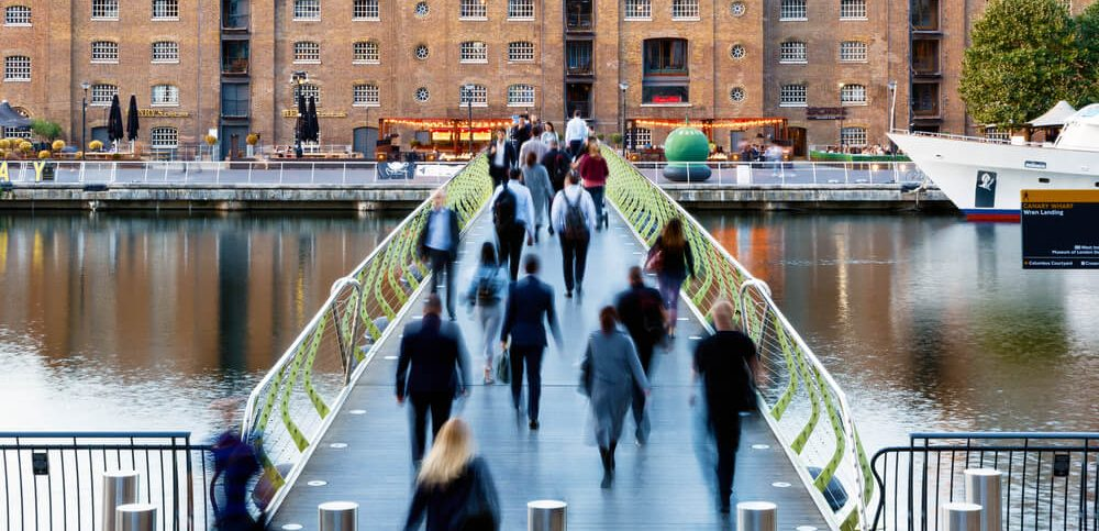People crossing the North Dock Footbridge from Canary Wharf to West India Quay