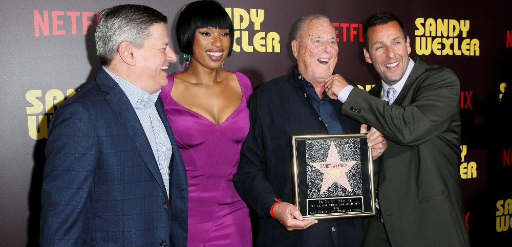 Netflix Chief Content Officer Ted Sarandos actors Jennifer Hudson and Adam Sandler present a gift to talent manager Sandy Wernick at a premiere for the Netflix original film Sandy Wexler in Los Angeles