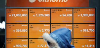 A man walks past an electric board showing exchange rates of various cryptocurrencies at Bithumb cryptocurrencies exchange in Seoul (1)