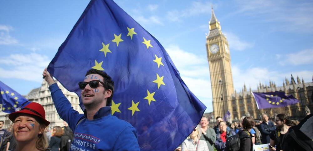 Central London, Uk. 25 March, 2017 A man holds an EU flag aloft at an anti-Brexit rally with Big Ben in the background.
