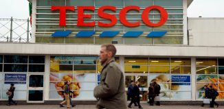 Pedestrians pass a Tesco supermarket in London