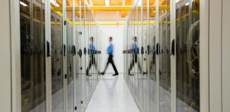 Technician walking in hallway of server room