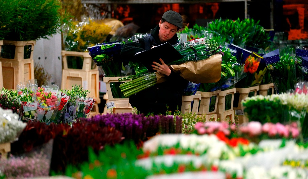 A customer checks his shopping list as he holds a bouquet at New Covent Garden wholesale flower market on the eve of St Valentines Day in London