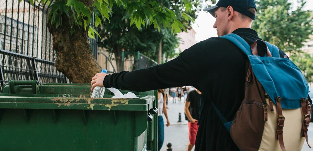 A tourist with a backpack and in a baseball cap on the street throws a plastic bottle into a container with waste.