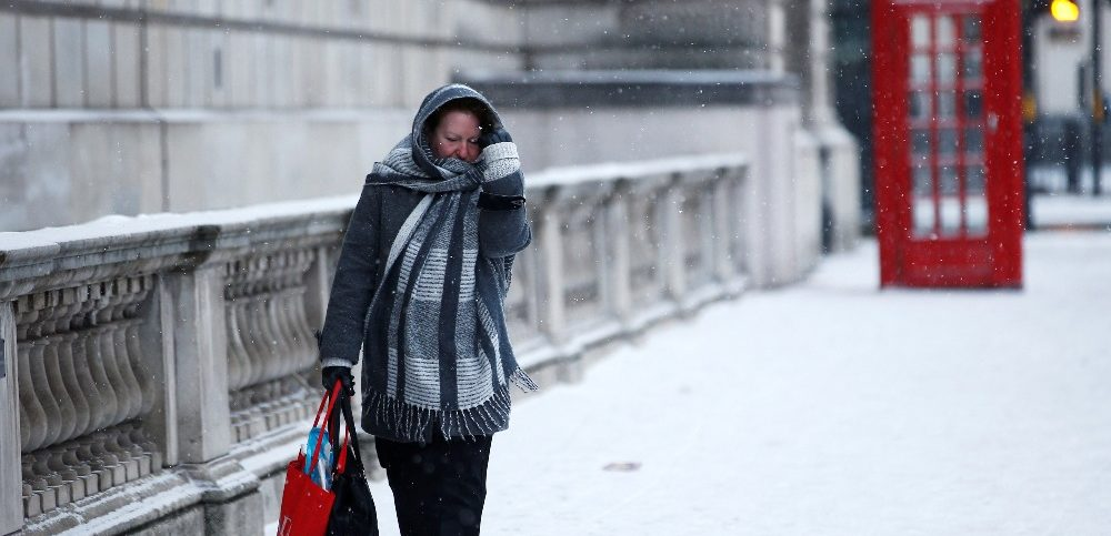 A woman walks through the snow storm in central London