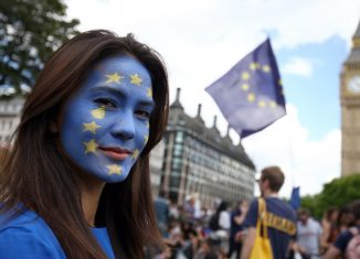 A woman with a painted face poses for a photograph during a demonstration against Britains decision to leave the European Union in central London