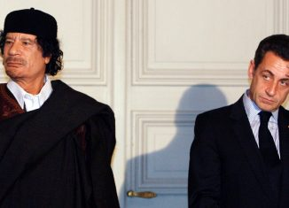 France's President Nicolas Sarkozy and Libyan leader Muammar Gaddafi leave the room after the signature of 10 billion euros of trade contracts in Paris