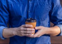 Man in jeans shirt holding cup of fresh coffee against brown background