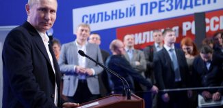Russian President and Presidential candidate Vladimir Putin attends a news conference at his campaign headquarters in Moscow