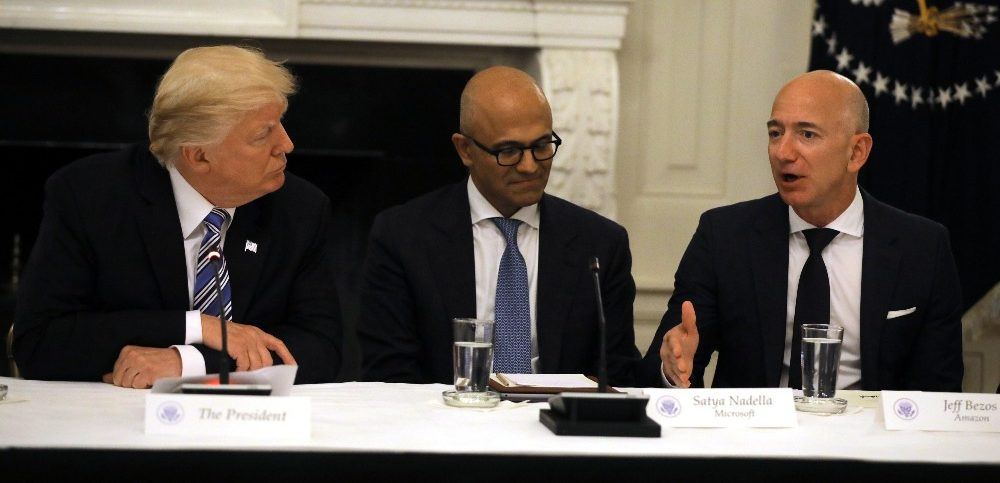 US President Donald Trump and Satya Nadella CEO of Microsoft Corporation listen as Jeff Bezos CEO of Amazon speaks during an American Technology Council roundtable