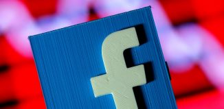 A-3D-printed-Facebook-logo-is-seen-in-front-of-a-displayed-stock-graph-in-this-illustration-taken