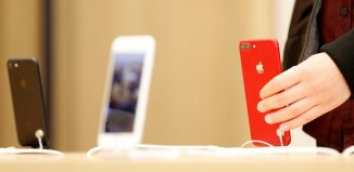 A person holds a red iPhone product at a Apple store in Nanjing