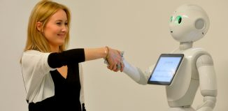 A press officer poses with Pepper the Humanoid Robot at the World of Me Store of the near future installation in London