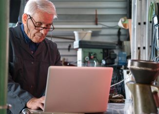 An active gray-haired senior working in his studio (1)