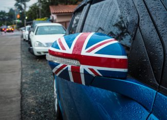 Close up on a side mirror of a car with the UK flag on it