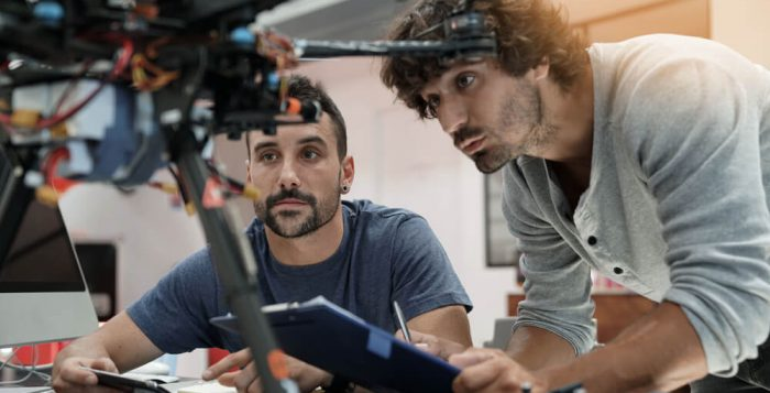 Engineer and technician working together on drone in office