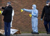 Police officers and forensic investigators examine the scene around Walthamstow Leisure Centre where a teenage boy was shot in London