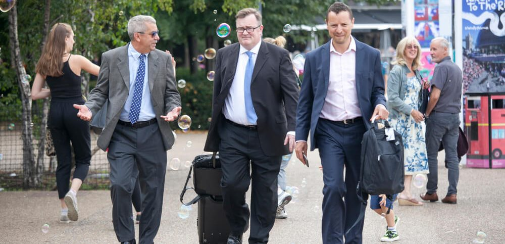 Businessmen with suitcases are walking along South bank