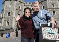 A couple wear Prince Harry and Meghan Markle face masks outside Windsor Castle in Windsor