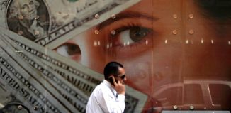 A man walks past an exchange bureau advertisement showing images of the US dollar in Cairo