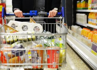 A shopper browses an aisle of a Tesco supermarket store