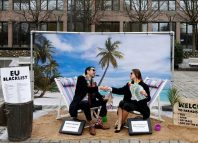 Activists stage a protest on a mock tropical island beach representing a tax haven outside a meeting of European Union finance ministers in Brussels