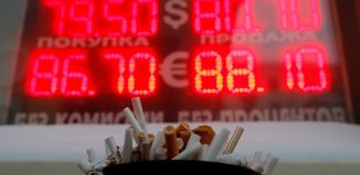 An ashtray filled with cigarette butts is seen in front of a board showing currency exchange rates of the US dollar and euro against rouble in Moscow