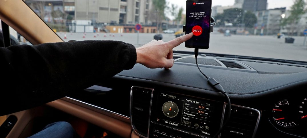 An engineer points to a Huawei Mate 10 Pro mobile used to control a driverless car during the Mobile World Congress in Barcelona.