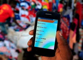 Man holds up his mobile phone showing a M-Pesa mobile money transaction page for the photographer at an open air market in Kibera in Kenyas capital Nairobi