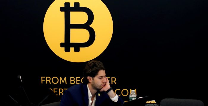 A-man-works-on-a-laptop-beneath-the-Bitcoin-logo-at-the-Consensus-2018-blockchain-technology-conference-in-New-York-City