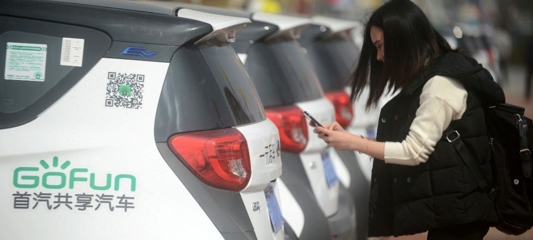 A woman uses her phone next to a Gofun electric car which is available for rental in Yangzhou Jiangsu province China