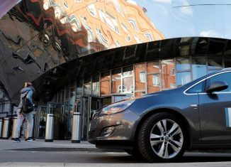 An Uber taxi is driven away from New Street Railway Station in Birmingham