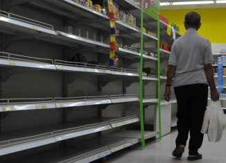 An unidentified shoppers browses empty shelves in a supermarket.