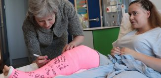Britains Prime Minister Theresa May signs the cast of patient Jade Myers 15 of London who broke her leg falling off a wall during a visit the Royal Free Hospital in London