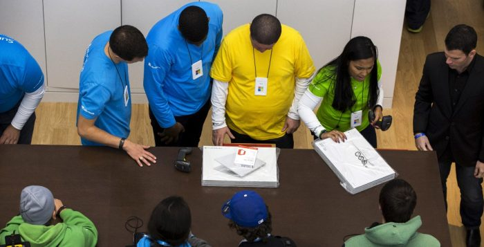Store employees help customers with their purchases during the grand opening of a flagship Microsoft Corp retail store in New York