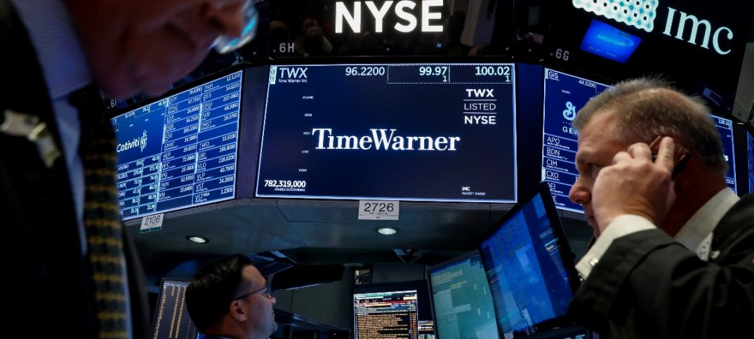Traders work at the post where Time Warner is traded on the floor of the NYSE in New York