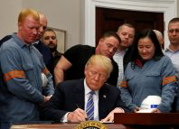 U.S. President Donald Trump signs a presidential proclamation placing tariffs on steel and aluminum imports.
