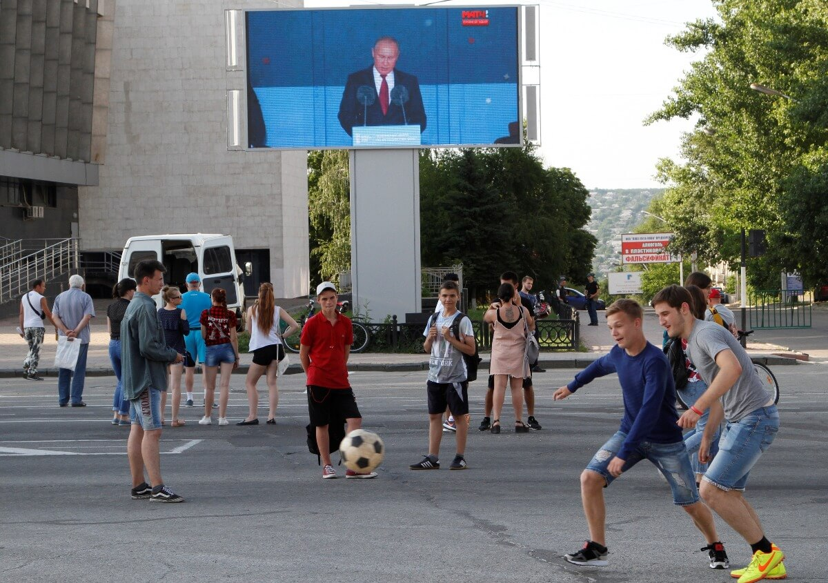 Youths play with a ball as Russian President Vladimir Putin is seen on a screen delivering a speech before the opening match